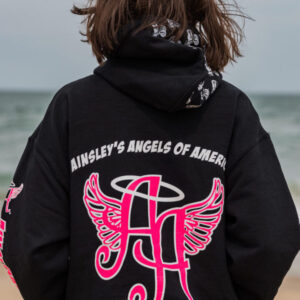 short-haired woman wearing a black Ainsley's Angels of America hoodie at the beach
