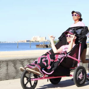 woman pushing a man in a jogger chair near the bay