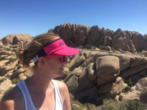 woman with a pink visor hat on a rocky background
