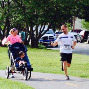 man running and doing an ok sign to a child in a jogger chair