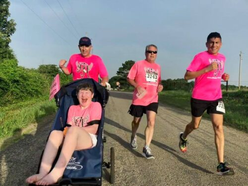 a child in a jogger chair, their Angel runner, and other two runners, all wearing pink