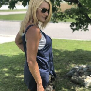 woman wearing a dark blue tank top and doing a side view pose