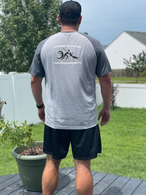man wearing a gray shirt with the logo of Ainsley's Angels of America race series at the back (different view)