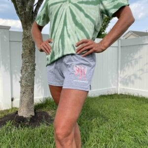 person wearing green tie-dye shirt and gray Ainsley's Angels of America shorts